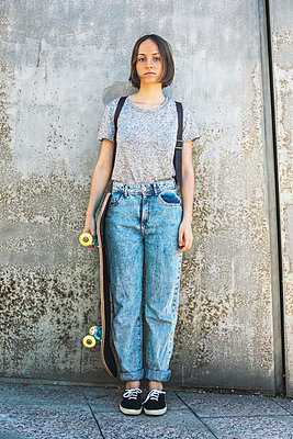 Spain, Barcelona, young female skate boarder standing in front of wall - p300m949761f by Bonninstudio