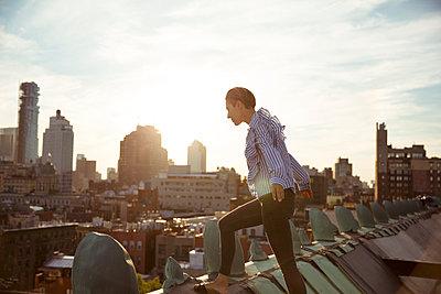 Balancierende junge Frau auf Dach - p432m1185603 von mia takahara