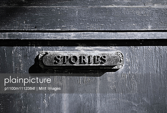 Stories plaque on a flat surface, a filing cabinet or drawer. - p1100m1112384f by Mint Images