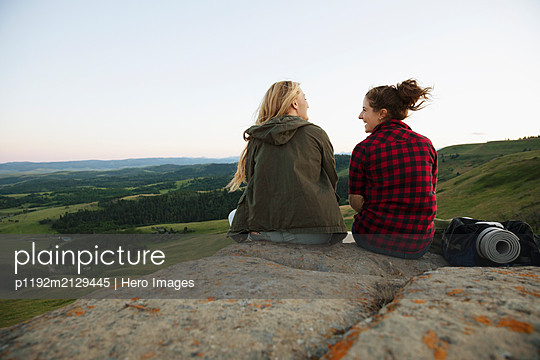 Two women sitting on rocks with camping gear - p1192m2129445 by Hero Images