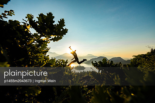 Person watching an early morning sunrise at Lake Bled - p1455m2043673 by Ingmar Wein