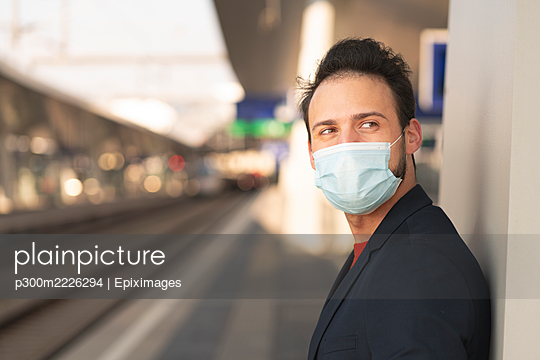 Male entrepreneur looking away while wearing protective mask on railroad platform - p300m2226294 by Epiximages
