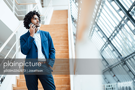 Handsome young male professional talking on mobile phone while standing against staircase in office - p300m2242973 by Joseffson