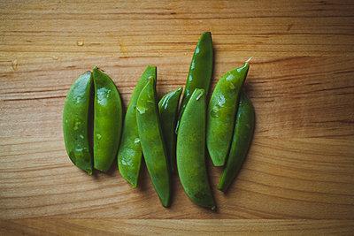 Overhead view of wet green peas on wooden table - p1166m1545136 by Cavan Social