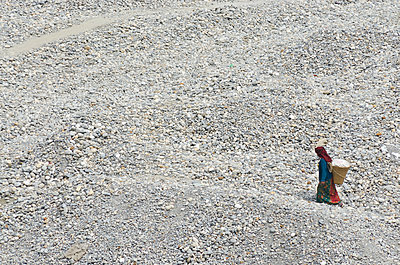 Woman Carrying Basket Through Stony Landscape - p1562m2158204 by chinch gryniewicz