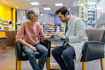 Pharmacist measuring blood sugar of customer in pharmacy - p300m1549446 by Mareen Fischinger