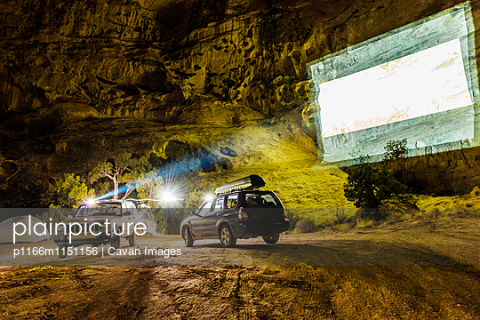 Off-road vehicles with projection screen on mountain at campsite - p1166m1151156 by Cavan Images