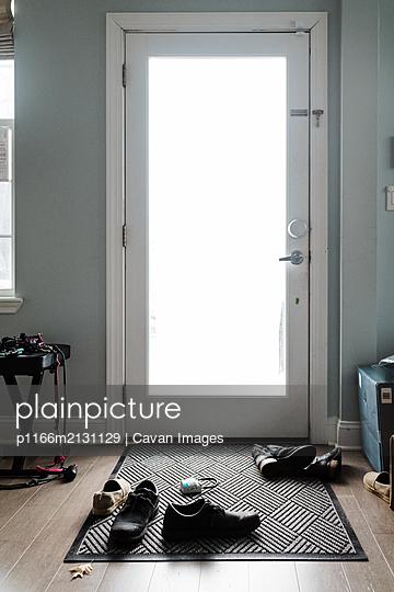 Messy shoes in front of door - p1166m2131129 by Cavan Images