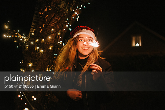 Young woman holding sparkler - p1507m2196555 by Emma Grann