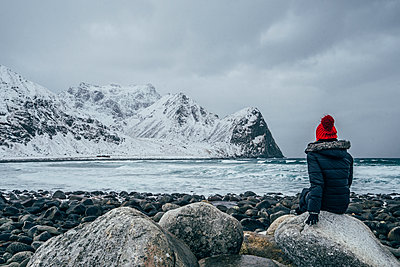 Woman in warm clothing enjoying remote snowy ocean and mountain view, Lofoten Islands, Norway - p1023m2067765 by Anna Wiewiora