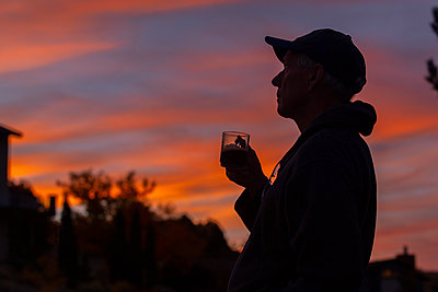 Silhouette of man holding coffee cup at sunset - p1427m2109951 by Steve Smith