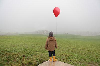 Kind mit rotem Ballom im Nebel - p1519m2134483 von Soany Guigand