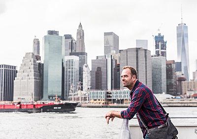 USA, New York City, man on ferry with Manhattan skyline in background - p300m1449376 by Uwe Umstätter