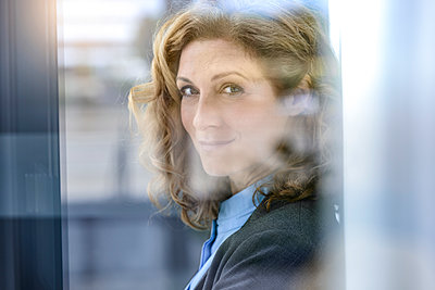 Portrait of a confident businesswoman behind windowpane - p300m2155535 by Buero Monaco
