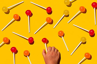 Studio shot of hand of baby girl picking up one of lollipops lying against yellow background - p300m2198282 by Gemma Ferrando