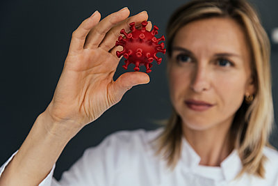 Female scientist looking at 3D model of SARS-CoV-2 virus - p300m2199262 by Mareen Fischinger