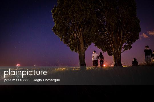 Menschen betrachten Feuerwerk in der Ferne - p829m1110836 von Régis Domergue