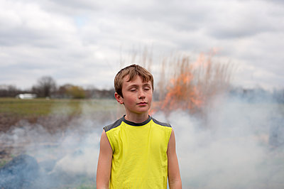 Boy in front of fire and smoke - p1169m2108497 by Tytia Habing