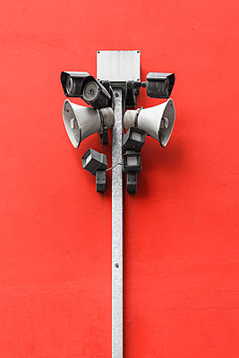 Loud speakers and security cameras on red wall - p1280m2182458 by Dave Wall