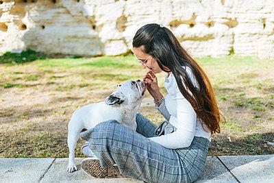 Woman feeding her dog outdoors - p300m2012696 von Kiko Jimenez