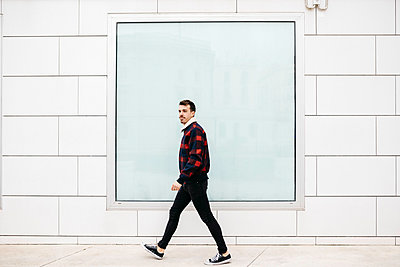 Young man with casual clothes walking with a white wall and a large window in the background - p300m2080628 by Josep Rovirosa