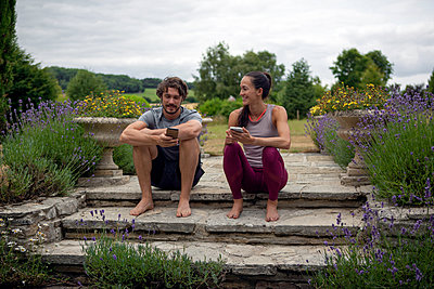 Man and woman practicing yoga in garden, looking at smartphones on patio - p429m2032220 by Image Source