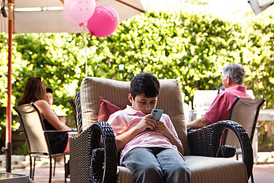 Bored boy using cell phone at party - p555m1420401 by Kyle Monk