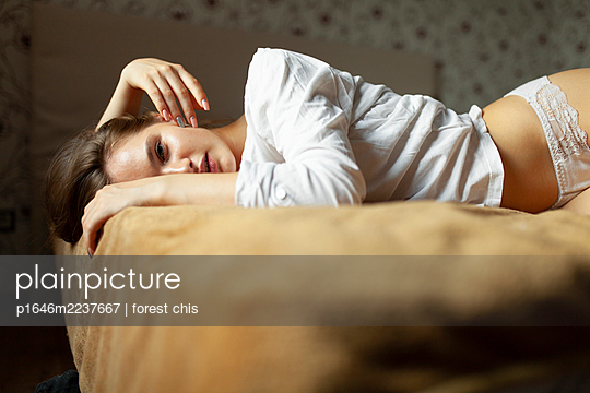 Young woman lying on bed - p1646m2237667 by Slava Chistyakov