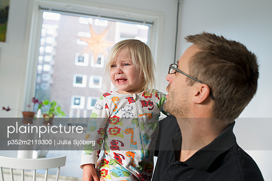 Father holding crying daughter - p352m2119300 by Julia Sjöberg