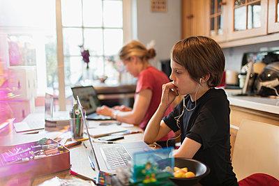 Focused boy homeschooling at laptop in kitchen - p1023m2201028 by Paul Bradbury