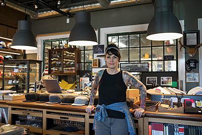 Portrait confident female motorcycle shop owner - p1192m1447373 by Hero Images