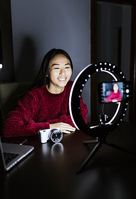 Smiling woman vlogging about new camera in darkroom - p300m2267039 by DREAMSTOCK1982