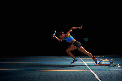 Young female athlete in relay race - p429m838964 by Peter Muller
