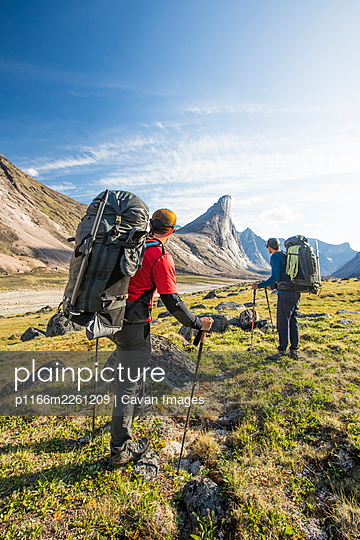 Backpackers look towards Mt. Thor, earth's greatest vertical drop. - p1166m2261209 by Cavan Images