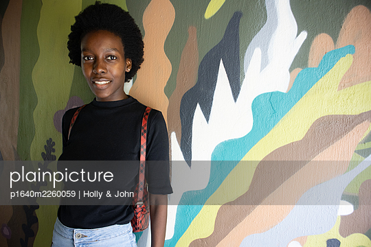Young African woman in front of a graffiti, portrait - p1640m2260059 by Holly & John