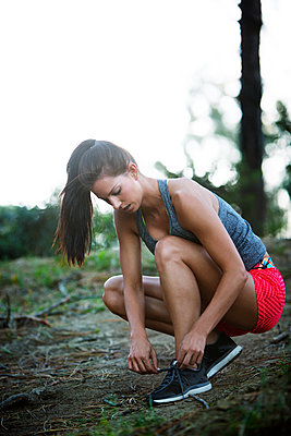 Full length of sporty woman tying shoelace in forest against clear sky - p1166m1080399f by John Trice