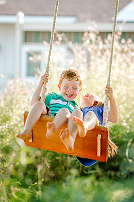 Cheerful siblings swinging on rope swing at front yard - p1166m1507985 by Cavan Images