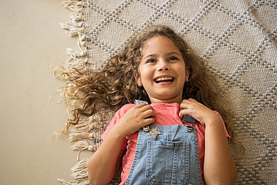 Little girl lies laughing on a carpet - p1640m2246136 by Holly & John