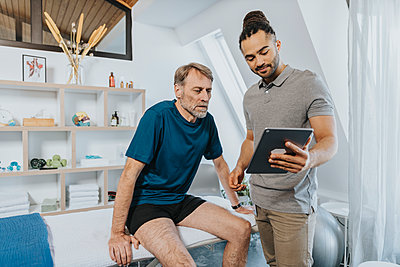 Male physiotherapist showing digital tablet to patient in practice - p300m2276799 by Mareen Fischinger