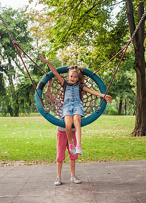 Child pushing girl on web swing - p429m2019420 by Seb Oliver