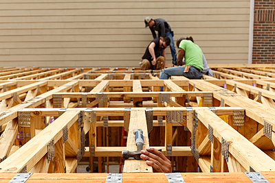 Hand reaching for hammer on the roof at construction site - p555m1522815 by Roberto Westbrook