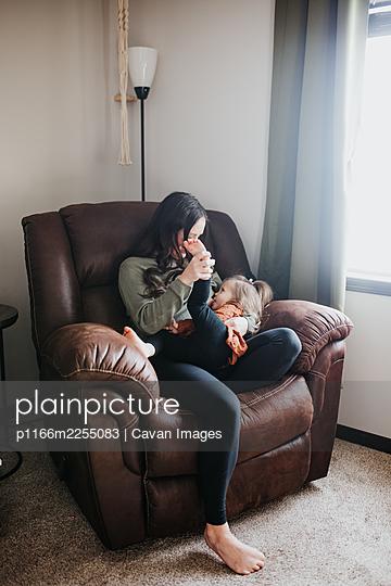 Mother breastfeeding toddler daughter in their home nursery - p1166m2255083 by Cavan Images