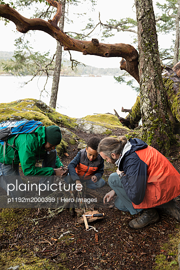 Trail guide teaching father and son how to build campfire in woods - p1192m2000399 by Hero Images