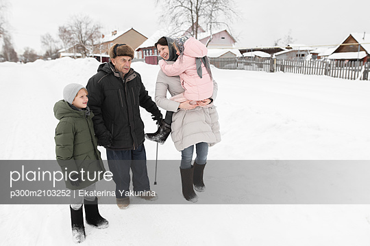 Grandfather together with daughter and grandchildren in snow - p300m2103252 by Ekaterina Yakunina