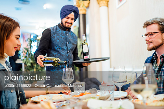Friends dining in an Indian restaurant, waiter pouring wine in glasses - p300m2166922 by Oscar Carrascosa Martinez
