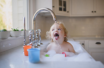 Cute shirtless girl drinking water from faucet while bathing in sink at home - p1166m2033905 by Cavan Images