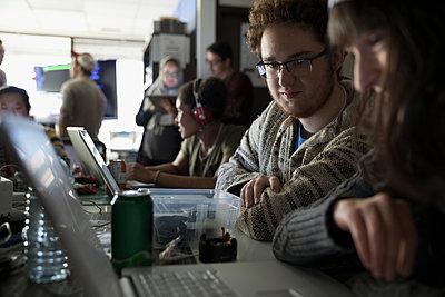 Hackers working hackathon at laptops in dark office - p1192m1202096 by Hero Images