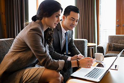 Business people meeting, using laptop in hotel lobby - p1192m2047107 by Hero Images