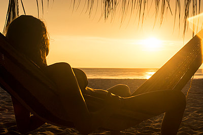 Woman watching the sunset from a hammock in Puerto Escondido, Mexico. - p1424m1500497 by Andres Valencia