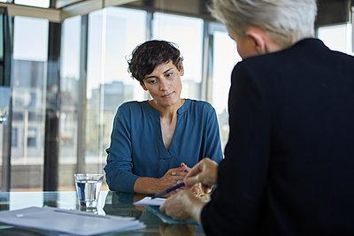 Two businesswomen talking at desk in office - p300m2081118 von Rainer Berg